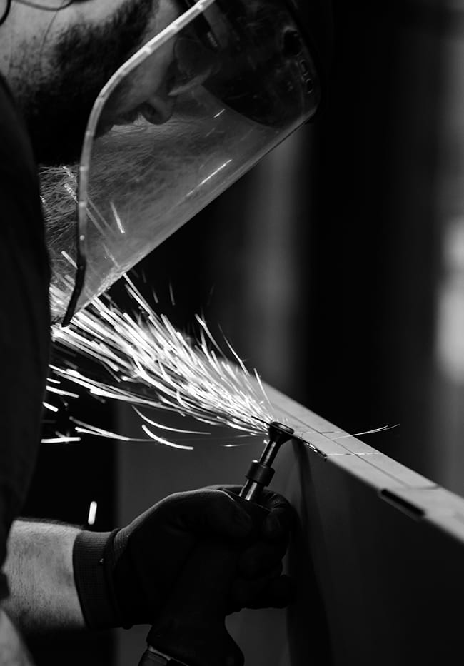 Black and white photo of a factory worker grinding metal with sparks flying