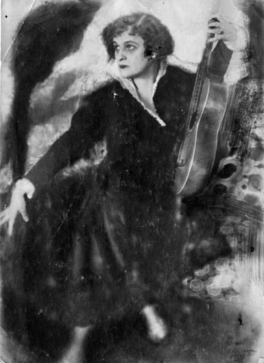 Photo of Teffi, seated, holding a guitar at her side