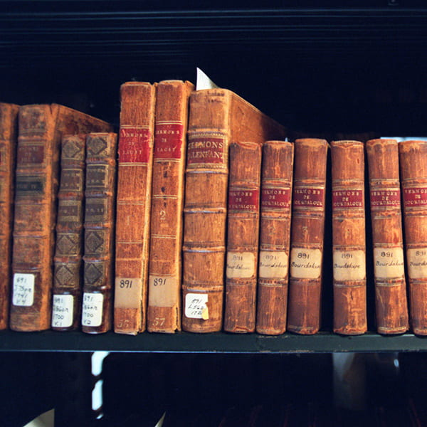 Photo of old books of sermons on the library shelves