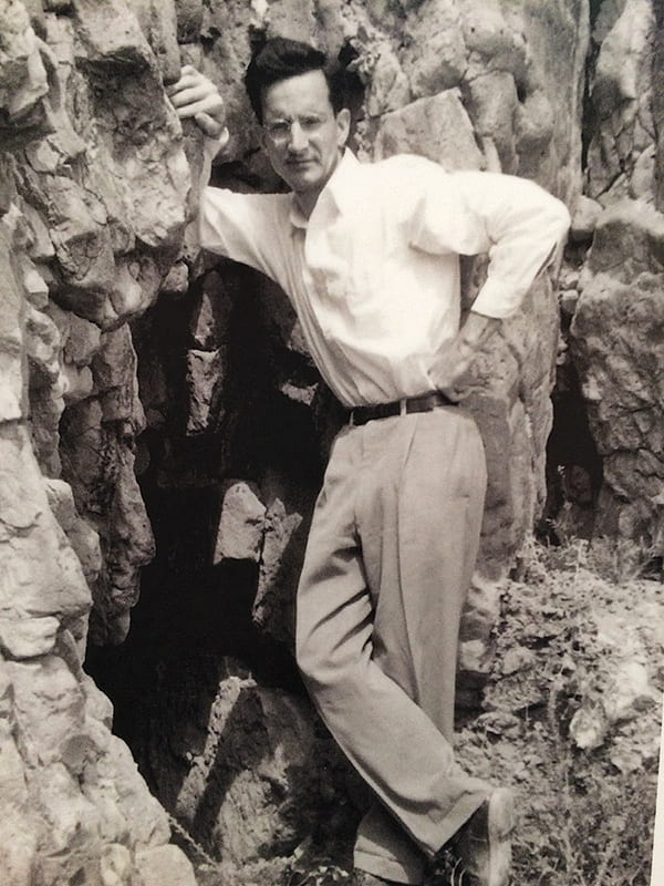 Frank Moore Cross standing in front of a cave