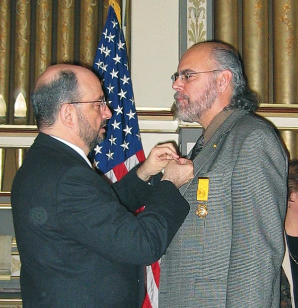 David Carrasco at an award ceremony, getting a ribbon pinned to his lapel