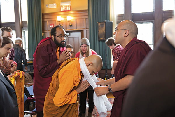 The Karmapa Lama draping a white khata cloth over a monk student's neck in the Braun Room