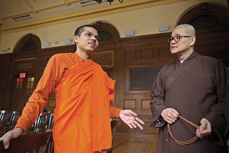 Two Buddhist monks standing in the chapel of Divinity Hall