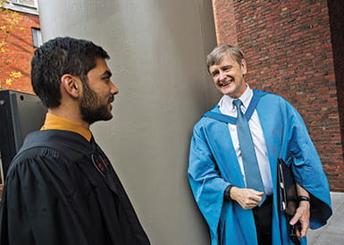 Dean Hempton speaking to a student, both dresses in academic robes