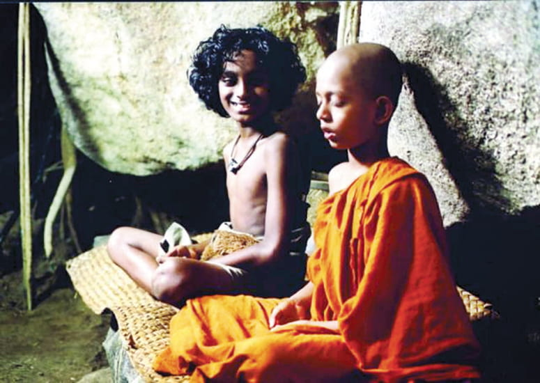 Film still of a young monk meditating next to his smiling friend from Suriya Arana
