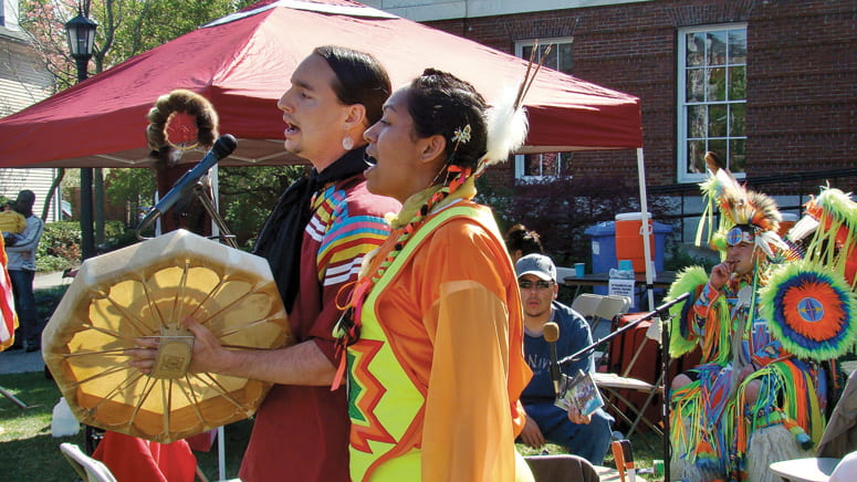 Photo of performers in traditional dress, drumming and singing at a PowWow on the Harvard campus