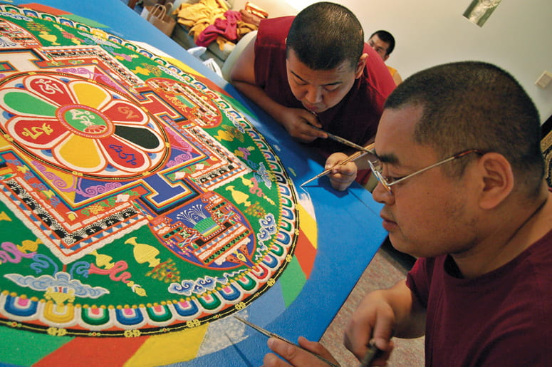 Two Buddhist monks filling in the edges of a sand mandala