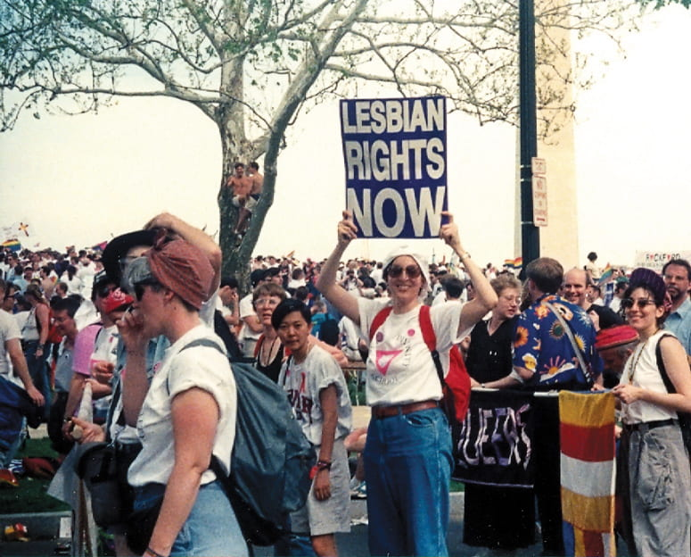 """Protest march, with woman holding up signs reading """"Lesbian Rights Now"""""""