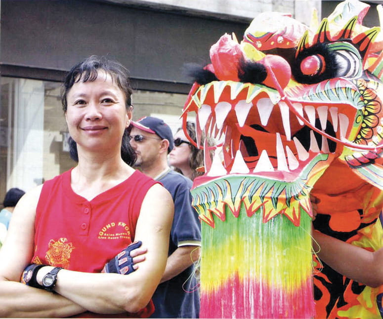 Woman standing next to a colorful dragon dance mask