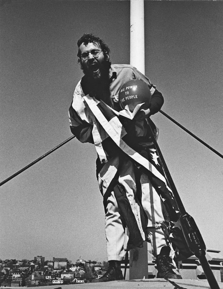 Man draped in American Flag, leaning away from flag pole, yelling towards the camera