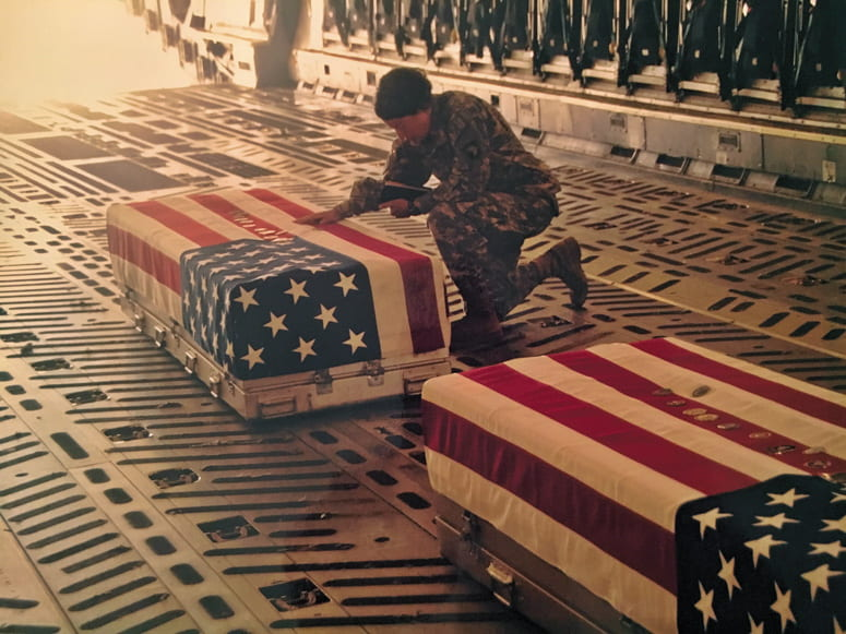 Military chaplain holding a bible and kneeling next to flag-draped coffins in the back of an airplane