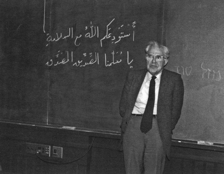 Wilfred Cantwell Smith standing in front of a chalkboard with Arabic writing on it