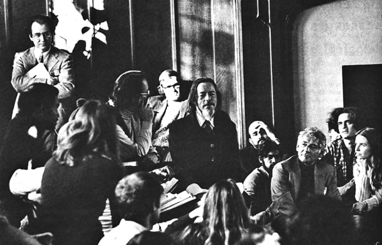 Alan Watts surrounded by students and faculty in the Braun Room