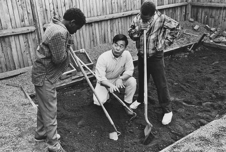 HDS student crouched down in an empty garden with two children, all holding gardening tools