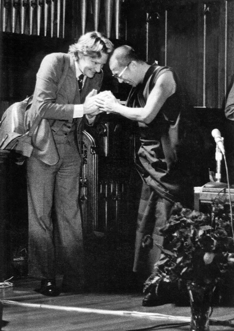 Photo of a the Dalai Lama touching Robert Thurman's hands as he bows