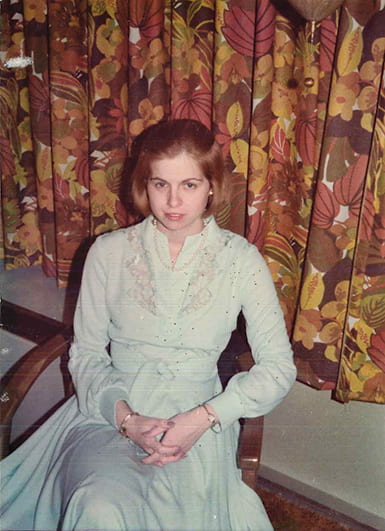 Snapshot of a young woman in a dress sitting in a chair