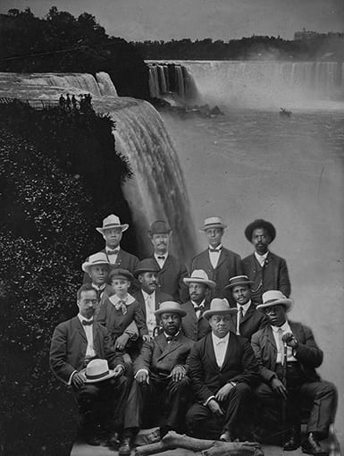 Photo of a group of African American men infront of a background showing Naigara Falls