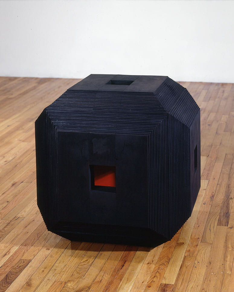 Photo of a black cube with a small opening to see a red interior