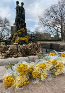 Bouquets of yellow flowers decorating a statue and left in front of it for people to take away