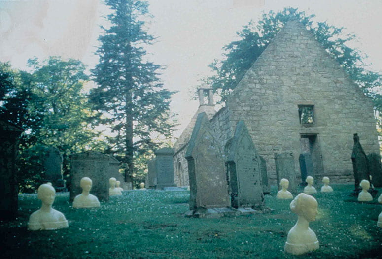 Photo of wax busts of women in an old churchyard