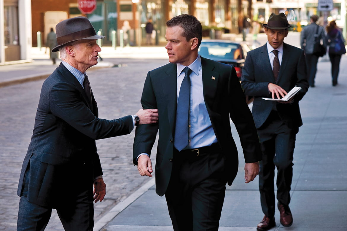Man walking down the street as another man touches his arm to get his attention and a third man follows behind looking at a notebook