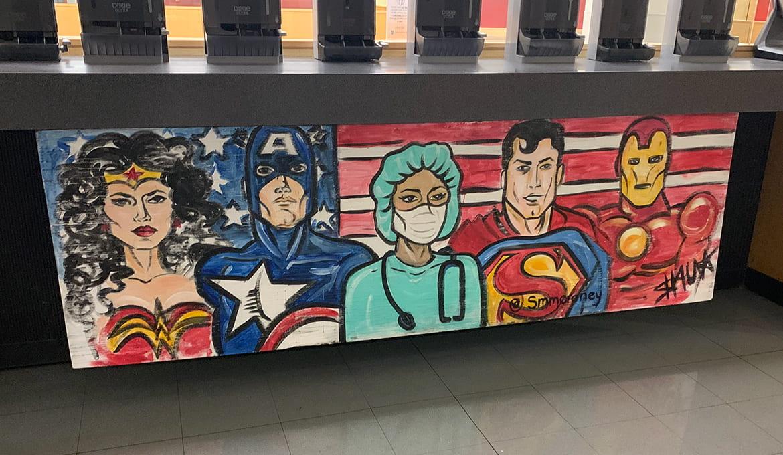 Mural of doctor alongside superheroes.