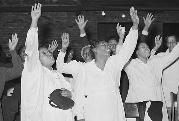 Pentecostal women with hand raised in praise during a worship service