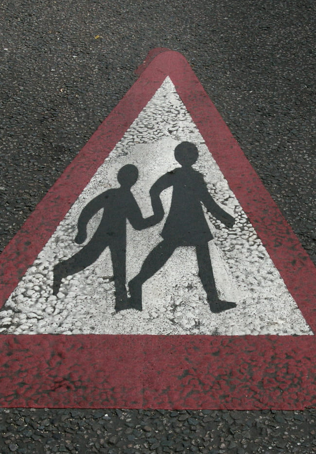 Photo of mother and child street crossing symbol painted on a street