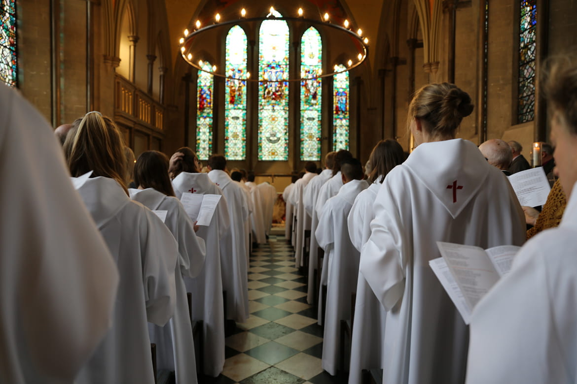 Young adults in white robes standing in worship inside a church sanctuary