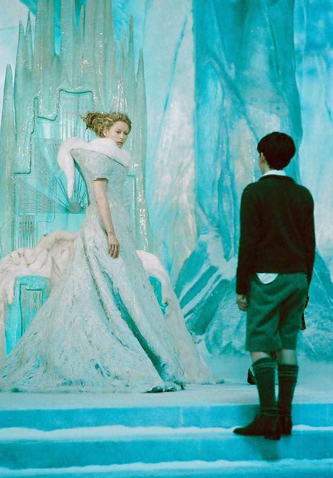 Woman in an ornate gown looking at a boy standing at attention, both inside an ice cavern