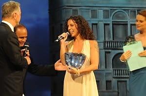 donna al centro con microfono e una coppa in mano