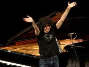 ragazzo a braccia spalancate davanti a pianoforte