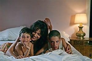 donna su letto con due bambini