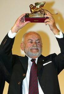 Dino de Laurentiis, uomo anziano che alza una statuetta di leone alato