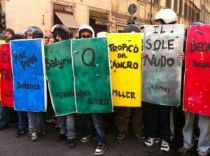 ragazzi con scudi colorati e caschi in una manifestazione di piazza