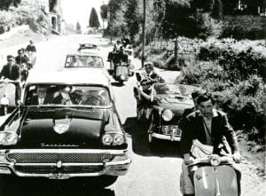 Foto d'epoca con persona in vespa in mezzo alle macchine