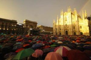 Il Duomo illuminato con arcobaleno e una folla di ombrelli sotto