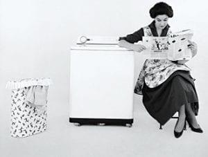 Donna legge il giornale mentre la lavatrice lavora