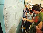 Ragazzi guardano gli scrutini appendi al muro del liceo