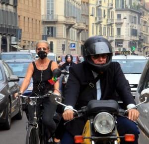 Uomo in moto nel traffico e donna in bici