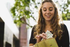 Ragazza conta soldi nel portafoglio