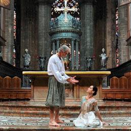 Attrice inginocchiata davanti a un uomo davanti a un altare
