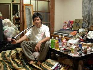 Un giapponese seduto per terra on una sciabola circondato da disordine