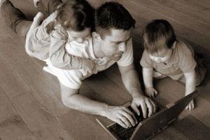 Padre con due bambini lavora al computer