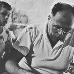 Danilo Dolci intento a scrivere con un bambino che lo osserva.