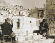 Due anziani sui gradini di una via di paese