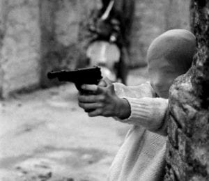bimbo mascherato che punta una pistola