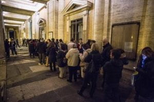 Gente in fila di notte al museo