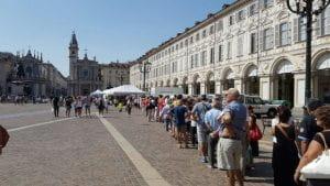 Gente in fila in una piazza di Torino.