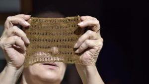 Donna che mostra un tessuto lavorato a mano.